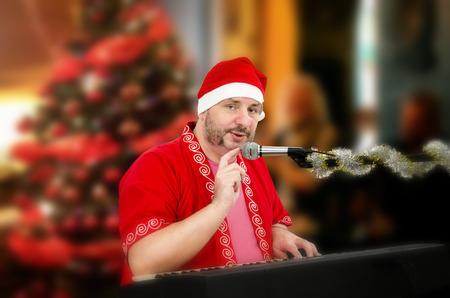 tapping: Uomo grasso maturo in costume di Babbo Natale toccando microfono