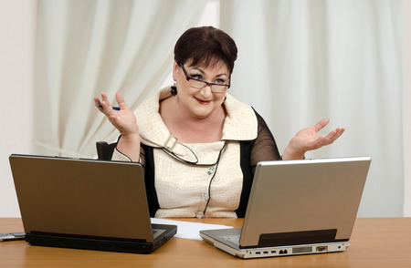 earns: Mature woman giving online math lessons and earns sufficient income  Stock Photo