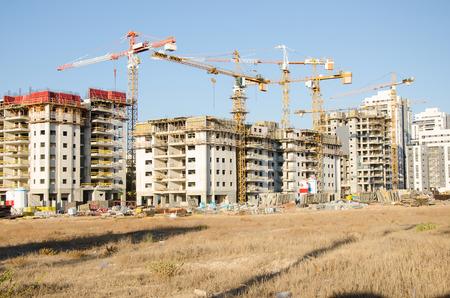 long shot: Pi� gru che lavorano in un'ampia area di costruzione in Israele Galili Street, Rishon LeZion, Israele. Grande quartiere residenziale in costruzione in luogo prato asciutto. Tiro lungo.