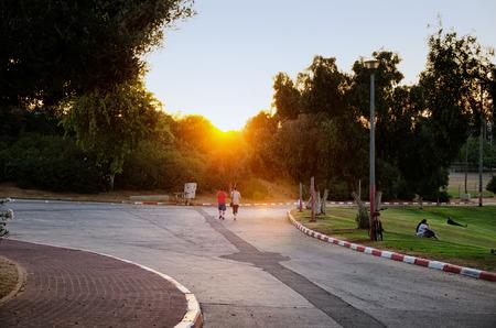 long shot: Guy coppia a piedi al tramonto. Girato a lungo in Amphipark a Rishon Le Zion, Israele Editoriali