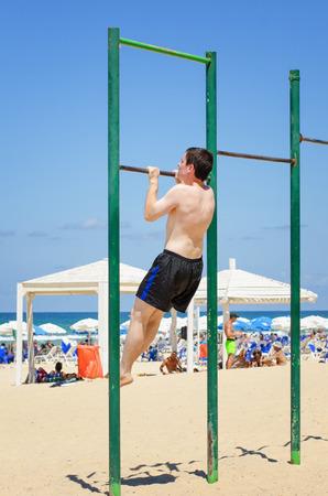 pull up: Giovane che si esercita su pull up bar in spiaggia Archivio Fotografico