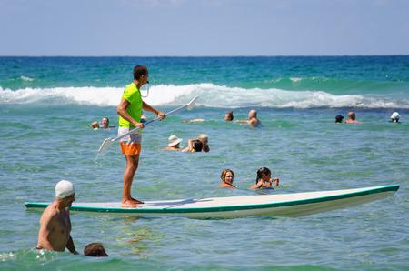 yam israel: Bat Yam, Israel - September 6, 2014: Bat Yam beach patrol. Beach lifeguard stand up paddling on the Mediterranean sea in Bat Yam city, Israel. People swim near a lifeguard