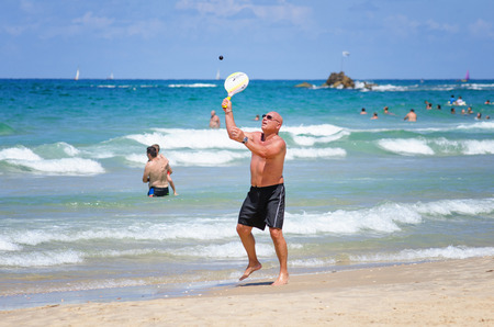yam israel: Bat Yam, Israel - September 6, 2014: Mature man plays Matkot in the beach of Bat Yam city. Matkot is the national Israeli beach sport. It is similar to tennis.