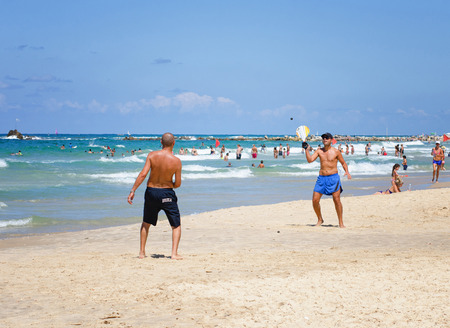 yam israel: Bat Yam, Israel - September 6, 2014: Two men play in the game likes beach tennis in Bat Yam city, Israel. It is Matkot.  Matkot is a game with no rules, no winners and no losers. In order to succeed, the players must put their full focus in the black rubb