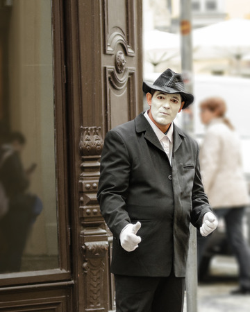 Prague, Czech Republic - September 26, 2014: Street mime with white face and gloves stands in Old Town Square the historic center of the Prague. He wears a rumpled black suit and hat. Mime has a sad sight.