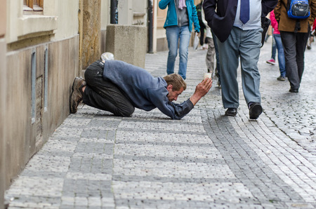 kneel down: Prague, Czech Republic - September 26, 2014: Beggar working in the Old Town. It seems he does not expect anything. Extended of his body are solely his arms, hands grasping paper cup to collect any spare change a pedestrian may decide to toss away.