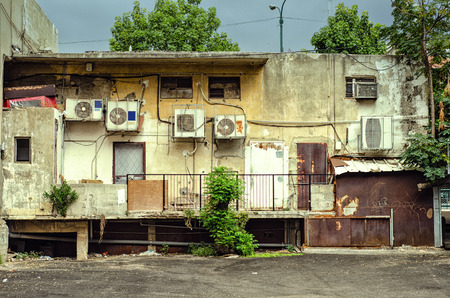 seamy: On the part of the backyard, fashion shop looks very badly. Shabby wall, rusty doors and windows, wires, air conditioners, etc. Stock Photo