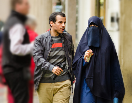 Prague, Czech Republic - September 26, 2014: Young Muslim couple walks down the street of Old Town. Woman wears traditional clothes, thereby leaving only the eyes visible. However, she holding a cell phone in right hand
