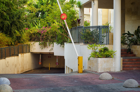 barrier gate: Rishon LeZion, Israel - September 3, 2014: The entrance to the underground parking of apartment building with opened barrier gate. Staircase leads into residential entrance on right side. Surrounded by trees and flowers Editorial