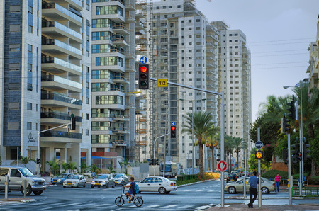Rishon LeZion, Israel - September 3, 2014: Unidentified young cyclist crossing Junction Israel Galili and Ha-Tkuma Streets in Rishon LeZion. There is huge residential buildings construction in new neighbourhood complex Upper West