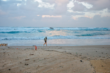yam israel: Bat Yam, Israel - December 11, 2012: Unidentified old man is going fast in the winter stormy beach in Bat Yam early morning. Bat Yam is a city located on Israel Editorial