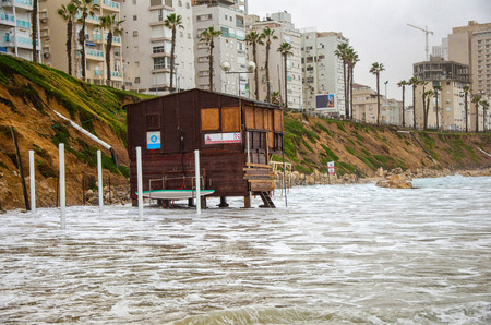yam israel: Bat Yam, Israel - December 11, 2012:  Tide is flooding at unused wooden lifeguard station in Bat Yam beach in the winter morning. Bat Yam is a city located on Israel