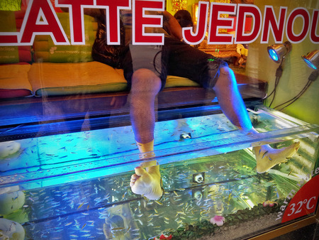 Man places his feet in tank of warm freshwater containing dozens of toothless Garra rufa fish. Fishes suck and gently nibble away at dry and dead skin Editorial