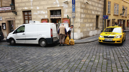 Distribution driver is delivering two mesh sacks of yellow potatoes to customer in Old Town Prague Stock Photo - 34588095
