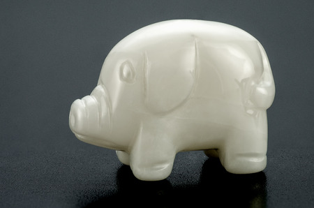 smoothen: Hand carved white onyx swine on black background