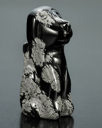 smoothen: Hand carved snowflake obsidian dog on black background Stock Photo