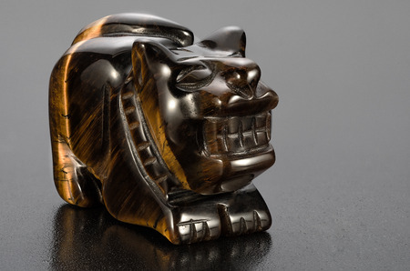 smoothen: Small carved tiger-eye tiger statuette on black background