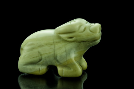 occupying: Hand carved butter jade ox on black background. Chinese sign Ox occupying the 2nd position on the Chinese Zodiac.