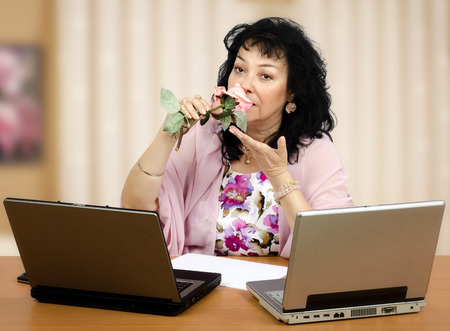Mature woman smelling pale pink rose in front of two laptops photo
