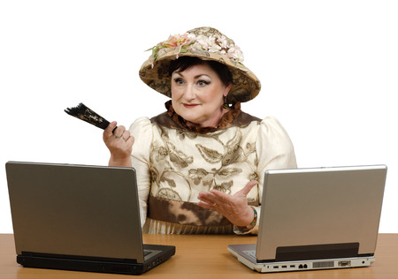 narrator: Portrait of online storyteller.  Old woman in antique clothing sitting in front of two laptops