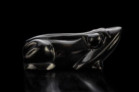 burnished: Black agate carved frog side view on black background