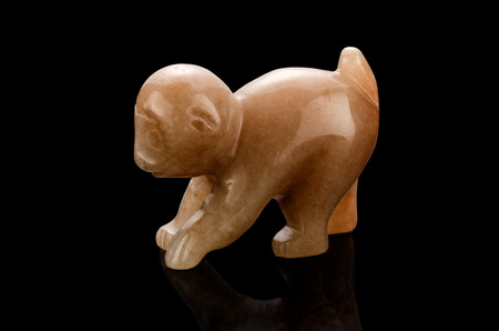 aragonite: Hand carved brown aragonite monkey statuette on black background Stock Photo