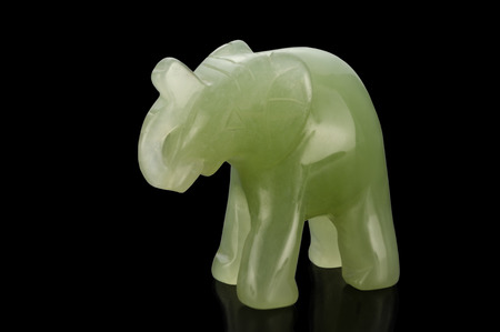 smoothen: Green jade elephant figurine on black background