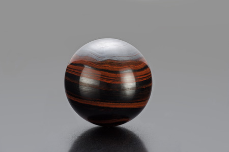 burnished: Iron tiger eye sphere on grey background