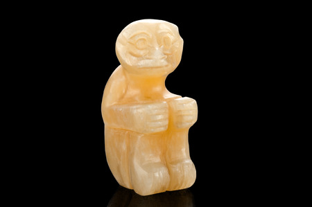 aragonite: Hand carved yellow aragonite sitting monkey figurine on black background