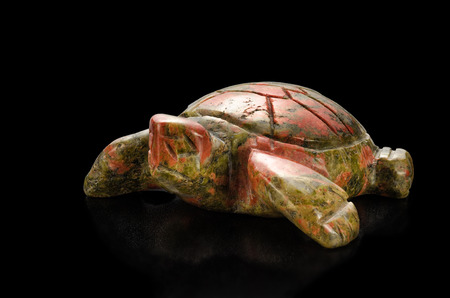 smoothen: Carved turtle unakite statuette on black background
