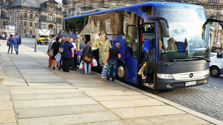 Dresden, Germany - September 30, 2014: Foreign tourist group is leaving Dresden on bus. They holding full shopping bags. Picture taken at Theaterplatz 3