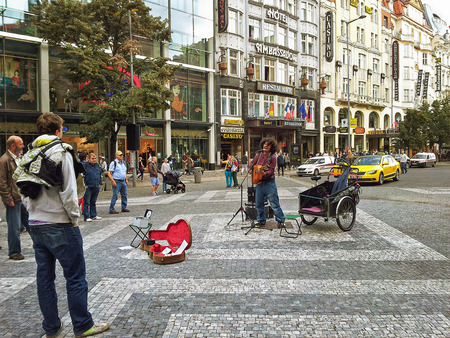busker: Prague, Czech Republic - October 1, 2014: South American busker performs at Wenceslas Square on the Ambassador Hotel background