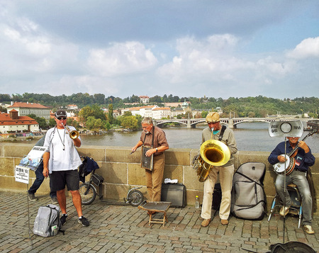 washboard: Prague, Czech Republic - October 2, 2014: The Bridge Band performs at Charles Bridge in Prague. Them playing the old brass, banjo, trumpet and a washboard on the Vltava river background