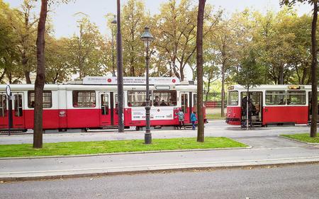 long shot: Vienna, Austria - 25 Settembre 2014: Due bambini non identificati intende prendere il tram alla fermata Burgring deserta. Tiro Long. Editoriali