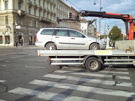 station wagon: Vienna, Austria - September 25, 2014: Metallic grey station wagon is wheel-clamped and removed away from city centre. Shooted in intersection of Bellariastrasse and Museumsplatz Streets Editorial