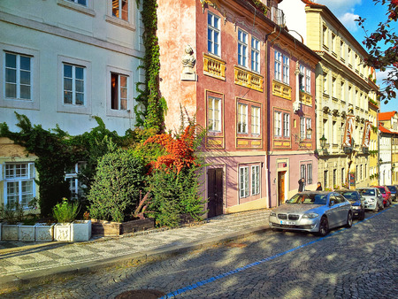 24 26: Prague, Czech Republic - September 27, 2014: Uvoz Street in bright sunny afternoon.  Light blue colour building is number 26. Terracotta colour is 24. Between them is growing green ivy