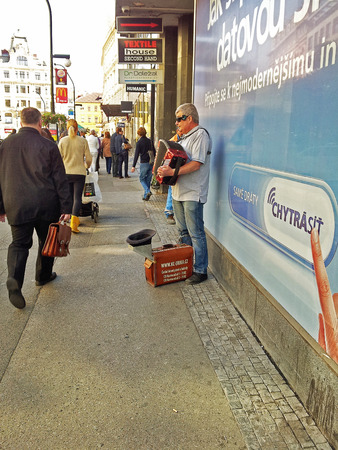 busker: Prague, Czech Republic - September 29, 2014:  Blind street musician plays the accordion in the centre of city.  Light brown briefcase for earnings is chained to his right leg.  Busker site address written on it.