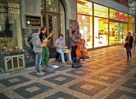 the quartet: Prague, Czech Republic - September 28, 2014: Jazz quartet of young street buskers performing at Wenceslas Square. Musicians play drums, double-bass, guitar and clarinet. Evening shot