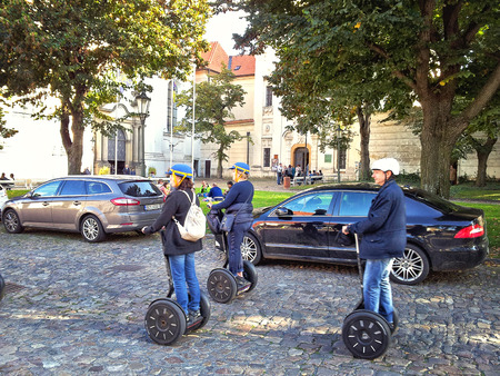go ahead: Prague, Czech Republic - September 27, 2014: Three riders Segway. Two mature women go ahead. The 60-year-old man behind. They move on old cobblestone. Strahov Monastery buildings are seen in background