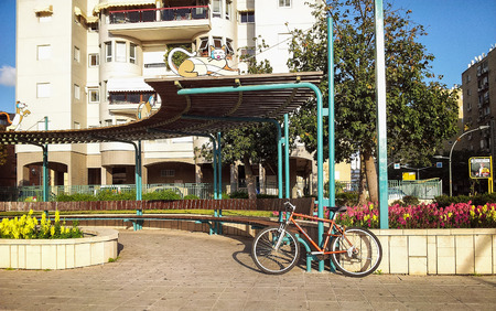 semicircular: Rishon Le Zion, Israel - March 15, 2015:  Brown bike is leaned on large semi-circular outdoor bench with pergola. Three metal coloured cat sculptures are walking on canopy