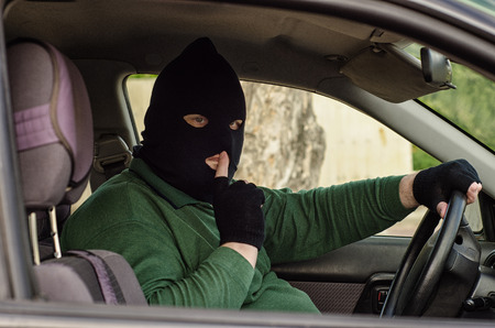 Robber in black balaclava puts his finger to his lips ambushing inside a car