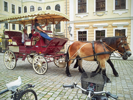 brougham: Dresden, Germany-September 30, 2014: Tourist couple enjoying horse-drawn carriage trip in city centre