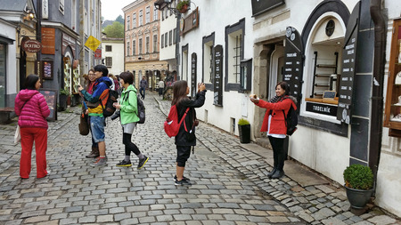 czech women: Cesky Krumlov, Czech Republic - October 1, 2014: There are six Asian tourists walking with cameras in the historical center of the city. Two of them taking picture of trdelnik
