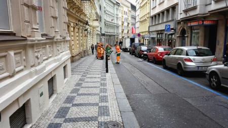 ve: Prague, Czech Republic - September 26, 2014: Two municipal sweepers in uniform cleaning Ve Smechkach Street with a vacuum