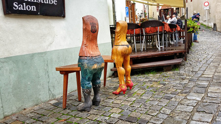 Cesky Krumlov, Czech Republic - October 1, 2014: Two funny carving wooden chairs are staying next by to entrance of restaurant Don Julius Stock Photo - 39324398