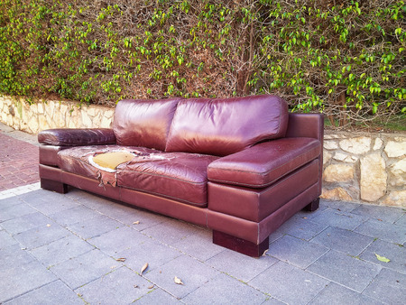 dumped: Ragged brown leather couch dumped on a street