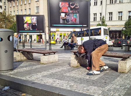 hobo: Prague Czech Republic  October 2 2014: Drunk hobo sleeping ridiculous position on bench in Wenceslas Square