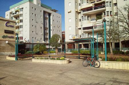 semicircular: Rishon Le Zion Israel  April 7 2015:  Empty large semicircular street bench with pergola