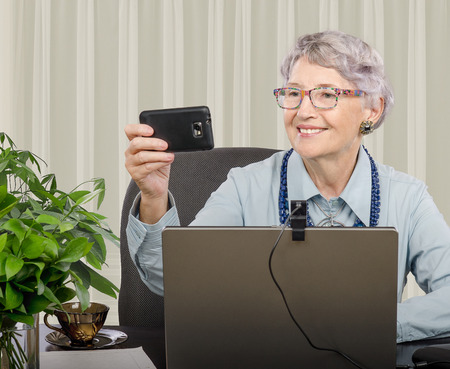telework: Cheerful old teacher sitting in online lesson and makes selfie photo on smartphone
