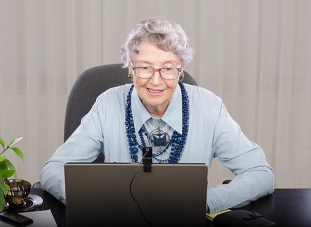 telework: Experienced tutor in blue blouse is teaching English language online